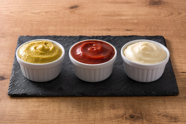 Ketchup,mustard and mayonnaise in a bowls on wooden table