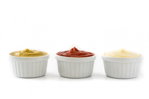 Ketchupmustard and mayonnaise in a bowls isolated on white background