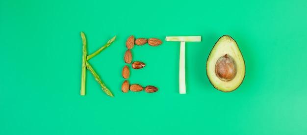 緑の背景にオーガニックアスパラガス、アーモンド、ブロッコリー、アボカドのketoアレンジメント。減量、、健康食品、ケトジェニックダイエット、低炭水化物、ベジタリアンのコンセプト