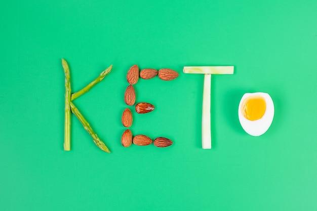緑の背景にオーガニックアスパラガス、アーモンド、ブロッコリー、ゆで卵のketoアレンジメント