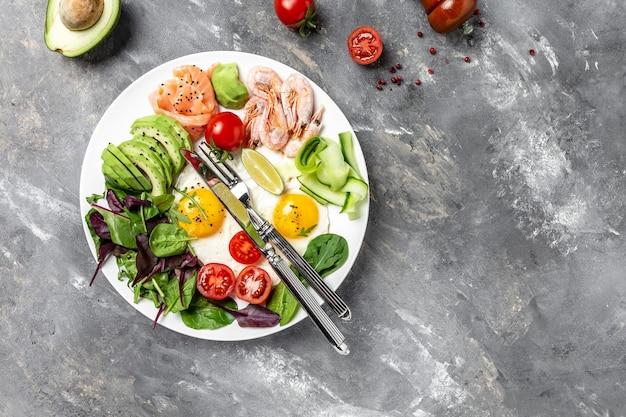 Кето-завтрак для кето-диеты. на завтрак лосось, вареные креветки, креветки, яичница, свежий салат, помидоры, огурцы и авокадо. вид сверху. концепция диеты с низким содержанием углеводов. диета с высоким содержанием жиров.