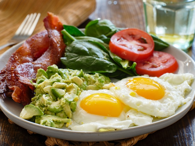 Keto breakfast plate with eggs bacon and mashed avocado