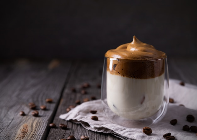 Keto dalgona whipped coffee with milk in a glass