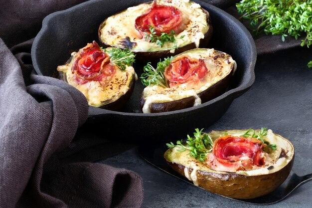 ケトダイエット料理:カリカリベーコン、溶けたチーズ、クレソンもやしの暗いアボカドボート