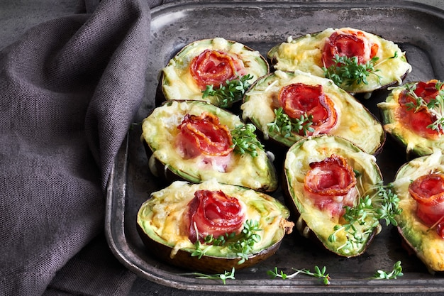 Keto diet dish: avocado boats with crunchy bacon, melted cheese and cress sprouts on dark