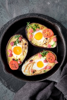 Keto diet dish: avocado boats with ham cubes, quail eggs, cheese and cherry tomatoes on iron cast skillet