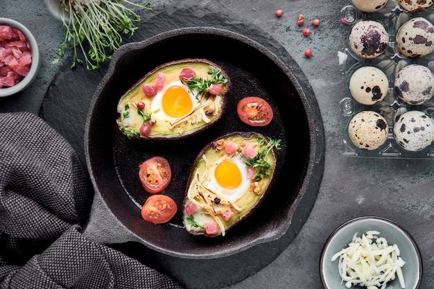 Keto diet dish: avocado boats with ham cubes, quail eggs, cheese, ingredients around