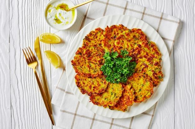 ケトダイエット料理:スイートオニオンのラトケスまたはグリーンハーブとライスのパンケーキ、白い木製のテーブルにパセリとヨーグルトソースを添えた白いプレートで提供、レモン、クローズアップ、上面図、コピースペース