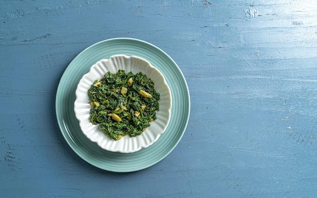 青い木製のテーブルトップビューの白いボウルと青いプレートのケトダイエット食品ほうれん草カレー