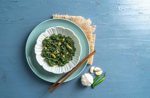 ケトダイエット食品ほうれん草カレーの白いボウルと青いプレート、箸とニンニクの唐辛子、青い木製のテーブルトップビューにヴィンテージレイヤー