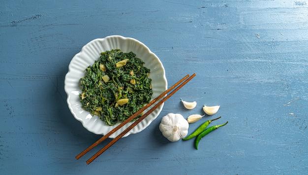 ケトダイエット食品ほうれん草カレー白いボウルと青いプレートに箸ガーリック唐辛子と青い木製のテーブルトップビュー
