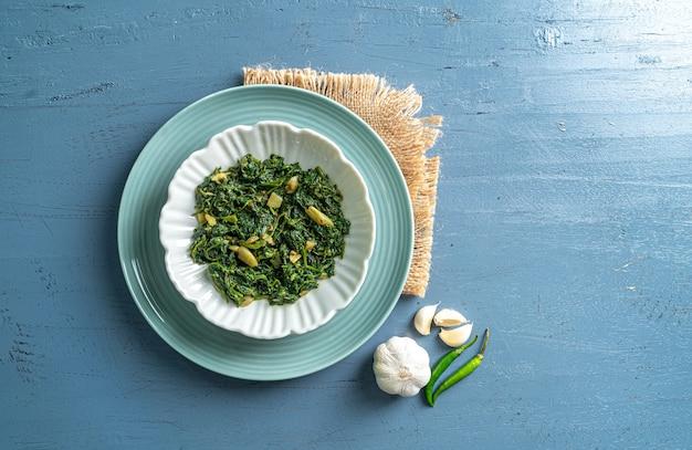 ケトダイエット食品ほうれん草カレーの白いボウルと青いプレートにニンニクと唐辛子、青い木製のテーブルトップビューにヴィンテージレイヤー