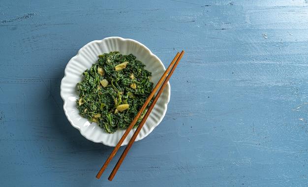 白いボウルと青いプレートにケトダイエット食品ほうれん草カレーと青い木製のテーブルトップビューに木製の箸
