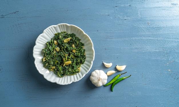 青い木製のテーブルトップビューに白いボウルと箸のニンニク唐辛子のケトダイエット食品ほうれん草カレー