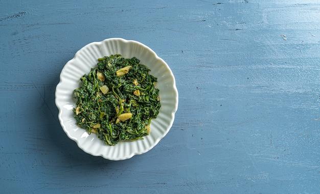青い木製のテーブルトップビューの白いボウルにケトダイエット食品ほうれん草カレー