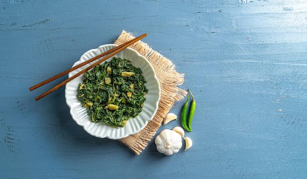青い木製のテーブルトップビューにヴィンテージレイヤーと箸とニンニク唐辛子と白いボウルでケトダイエット食品ほうれん草カレー
