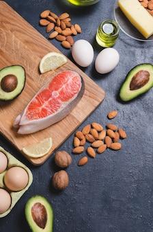 Кето диета, здоровая пища с низким содержанием углеводов. авокадо, рыба, масло, орехи на черном фоне