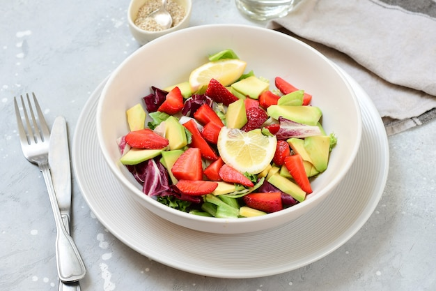 Keto food delicious avocado salad with  strawberries on a white plate.