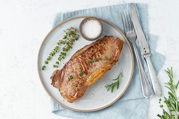 Keto ketogenic diet beef steak, striploin on gray plate on white