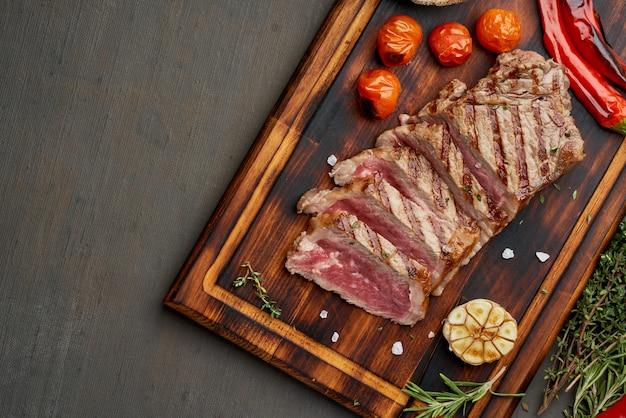 Кето-кетогенная диета на гриле, жареный бифштекс, полоска на разделочной доске на темно-коричневом столе