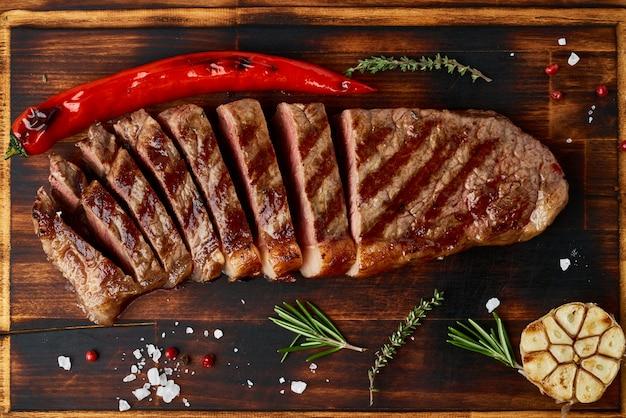 ケトケトジェニックダイエットミディアムビーフステーキ、まな板の上の焼きサーロイン。肉を使った古食品のレシピ