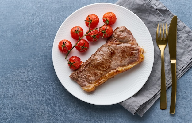 Keto ketogenic diet steak with tomatoes on dark background