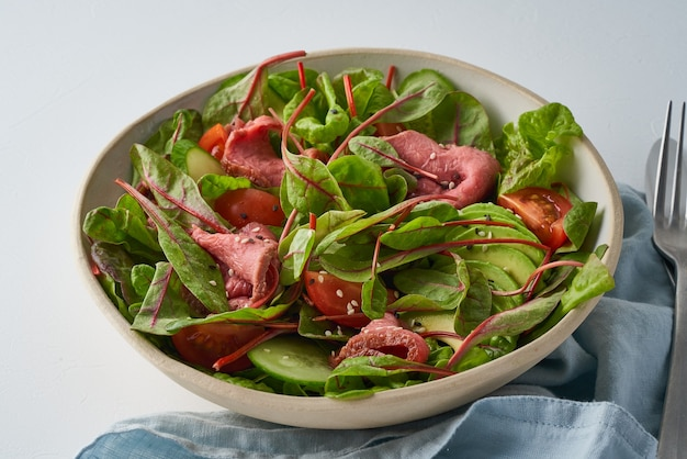 Keto salad with roast beef meat sous vide tomatoes cucumbers avocado on pastel linen tablecloth