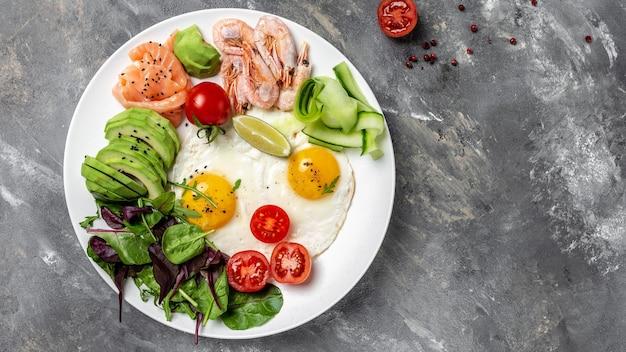 Кето-завтрак с лососем, вареными креветками, креветками, яичницей, свежим салатом, помидорами, огурцами и авокадо. концепция здорового питания. меню рецепт место для текста, вид сверху.