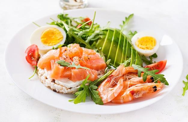 Кетогенный диетический завтрак. салат из соленого лосося с вареными креветками, креветками, помидорами, рукколой, яйцом и авокадо. кето, палео-ланч.