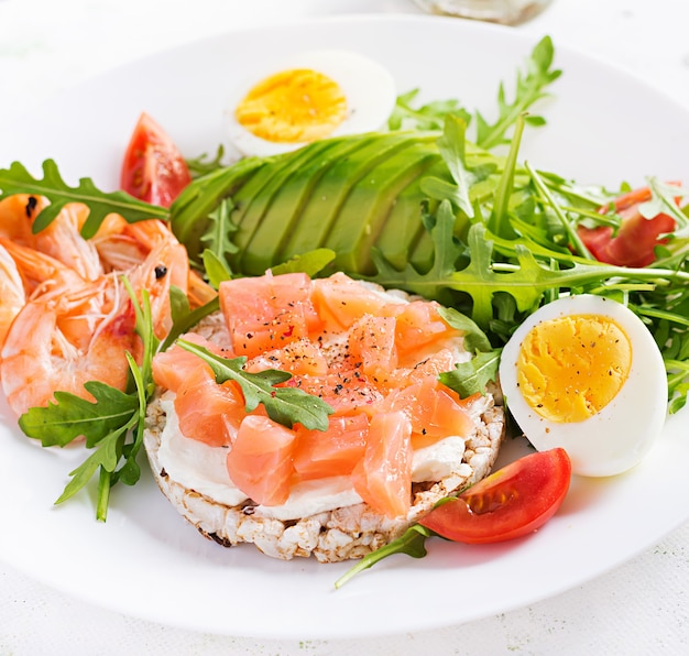 Ketogenic diet breakfast. salt salmon salad with boiled shrimps, prawns, tomatoes, arugula, eggs and avocado. keto, paleo lunch.