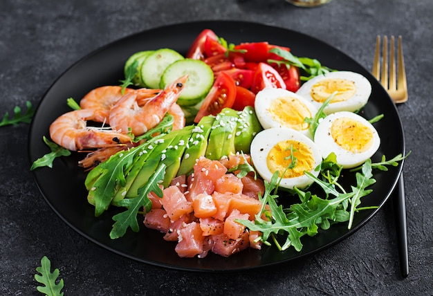 Ketogenic diet breakfast. salt salmon salad with boiled shrimps, prawns, tomatoes, cucumbers, arugula, eggs and avocado. keto, paleo lunch.