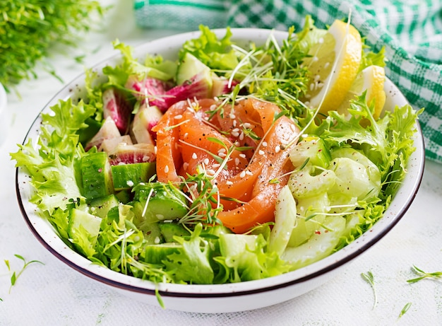 Ketogenic diet breakfast. salt salmon salad with greens, cucumbers, celery and watermelon radish. keto, paleo lunch.