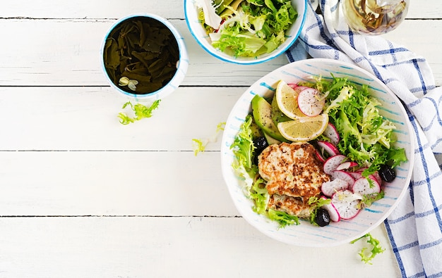 Ketogenic diet. buddha bowl dish with  chicken burger, avocado, radish and black olives. detox and healthy concept. keto food. overhead, top view, flat lay
