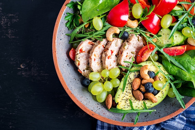 Ketogenic diet. buddha bowl dish with meatloaf, avocado, sweet pepper, tomato, cucumber, berries and nuts. detox and healthy superfoods bowl concept. overhead, top view, flat lay