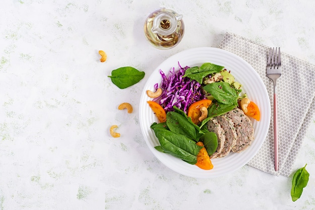 Ketogenic diet. buddha bowl dish with meatloaf, chicken meat, avocado, cabbage and nuts. detox and healthy concept. keto food. overhead, top view, flat lay