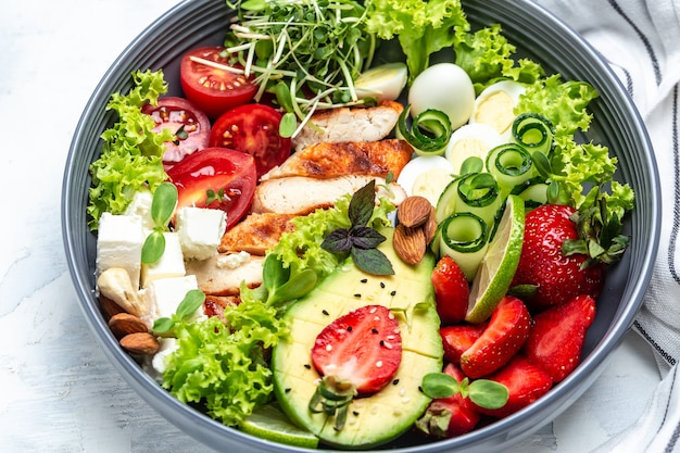 Ketogenic diet. chicken salad with avocado, feta cheese, quail eggs, strawberries, nuts and lettuce on white background. keto paleo breakfast. delicious balanced food concept.