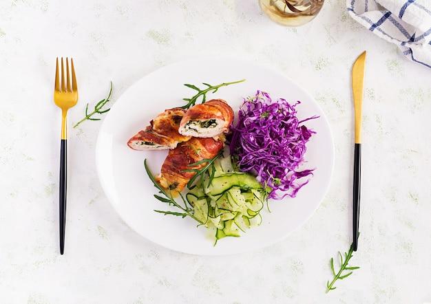 Кетогенная диета. обеденное блюдо с куриным мясным рулетом, беконом и салатом из красной капусты, огурцов, рукколы. детокс и здоровая концепция. кето-еда. накладные, вид сверху, плоская планировка