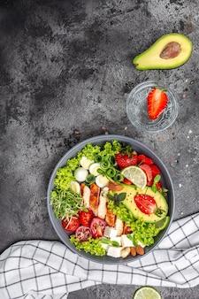 Кетогенное диетическое питание, куриное филе, киноа, авокадо, авокадо, сыр фета, перепелиные яйца, клубника, орехи и листья салата. концепция здорового питания, вертикальное изображение. вид сверху. место для текста