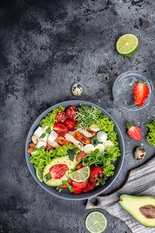 케토제닉 다이어트 식품, 치킨 필레, 퀴노아, 아보카도, 아보카도, 페타 치즈, 메추라기 알, 딸기, 견과류, 상추. 건강한 식사 개념, 수직 이미지입니다. 평면도. 텍스트를 위한 장소
