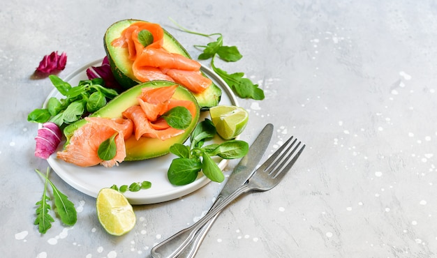 Ketogenic diet food salmon and avocado salad with arugula and lime. keto food
