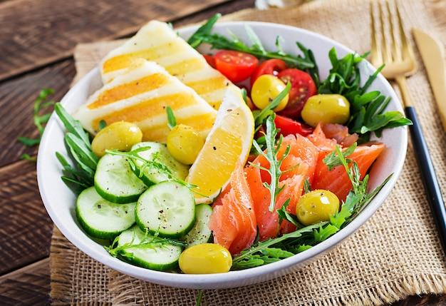 Кетогенная, кето-диета. соленый лосось, сыр халуми на гриле, помидоры черри и салат из огурцов с оливками в белой миске. здоровая пища.