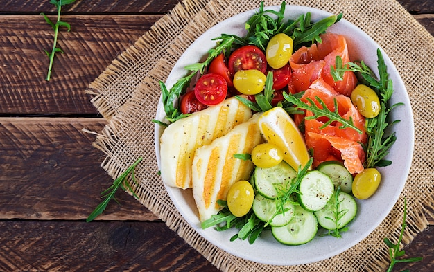 Ketogenic, keto diet. salted salmon, grilled halloumi cheese, cherry tomatoes and cucumber salad with  olives in white bowl. healthy food. top view, above