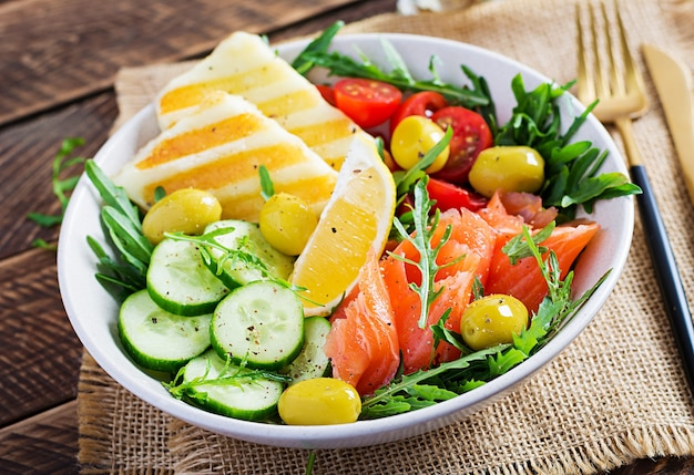 Ketogenic, keto diet. salted salmon, grilled halloumi cheese, cherry tomatoes and cucumber salad with  olives in white bowl. healthy food.