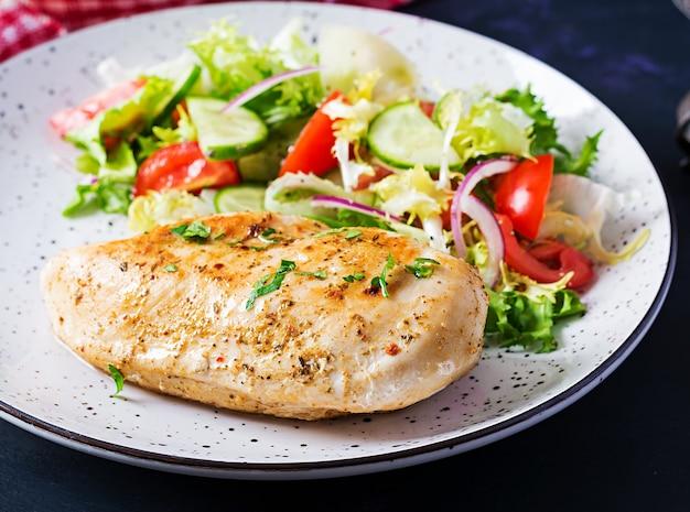 Кетогенная, кето-пища. жареное куриное филе и салат из свежих овощей из помидоров, огурцов и салата. куриное мясо с салатом. здоровая пища.