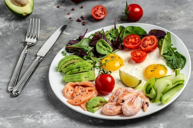 Кетогенный низкоуглеводный лосось, вареные креветки, креветки, яичница, свежий салат, помидоры, огурцы и авокадо. вид сверху.
