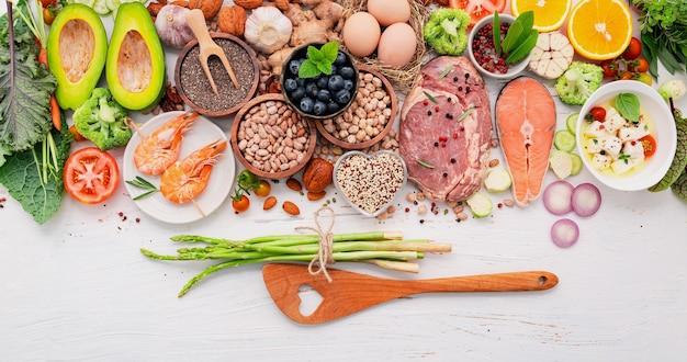 케톤 생성 저탄수화물 다이어트 개념. 건강 식품 선택을 위한 재료는 나무 배경에 설정되어 있습니다.