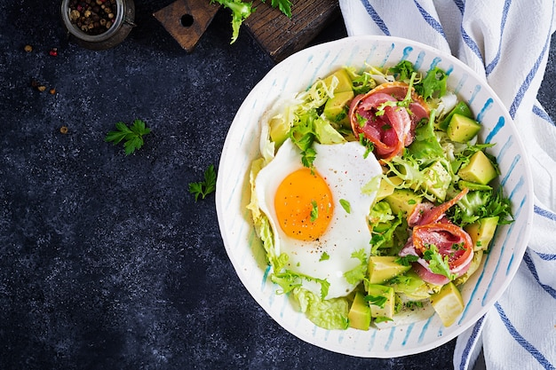 Ketogenic, paleo diet. fried egg, prosciutto, avocado and fresh salad.  keto breakfast. brunch.  top view, overhead, flat lay