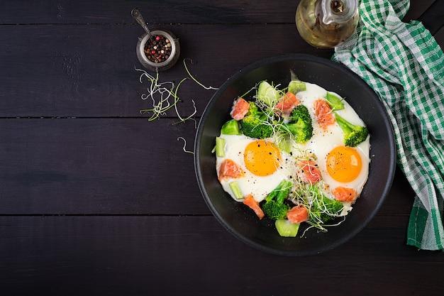 Ketogenic/paleo diet. fried eggs, salmon, broccoli and microgreen.  keto breakfast. brunch.  top view, overhead