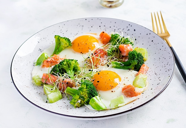 Ketogenic/paleo diet. fried eggs, salmon, broccoli and microgreen.  keto breakfast. brunch.