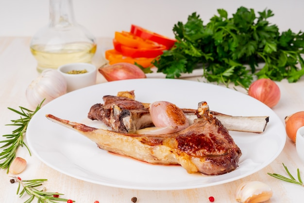 Ketogenic, paleo, lchf diet - fat fried lamb ribs on white plate with vegetable